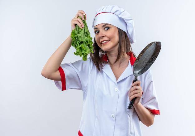 Opgewonden jonge vrouwelijke kok die chef-kok uniform draagt die salade met pan houdt die op witte achtergrond wordt geïsoleerd