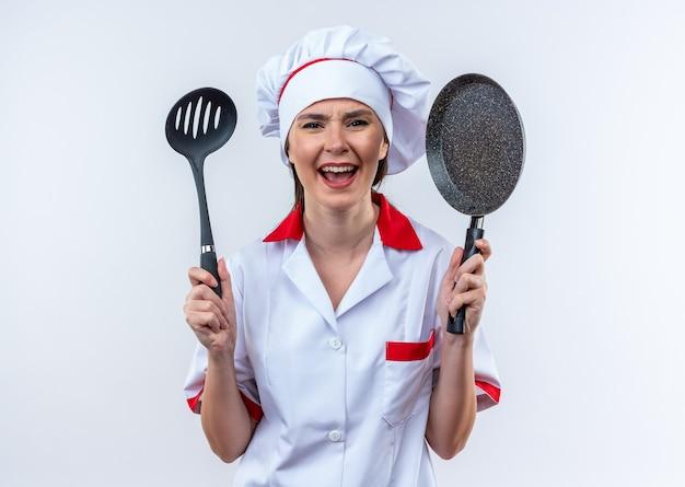 Opgewonden jonge vrouwelijke kok die een chef-kok uniform draagt en een spatel vasthoudt met een koekenpan geïsoleerd op een witte achtergrond