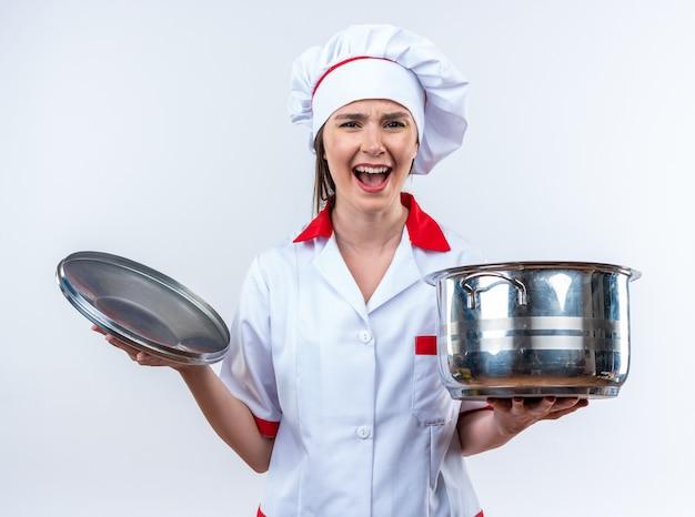 Opgewonden jonge vrouwelijke kok met een uniform van de chef-kok die een steelpan met deksel vasthoudt die op een witte achtergrond wordt geïsoleerd