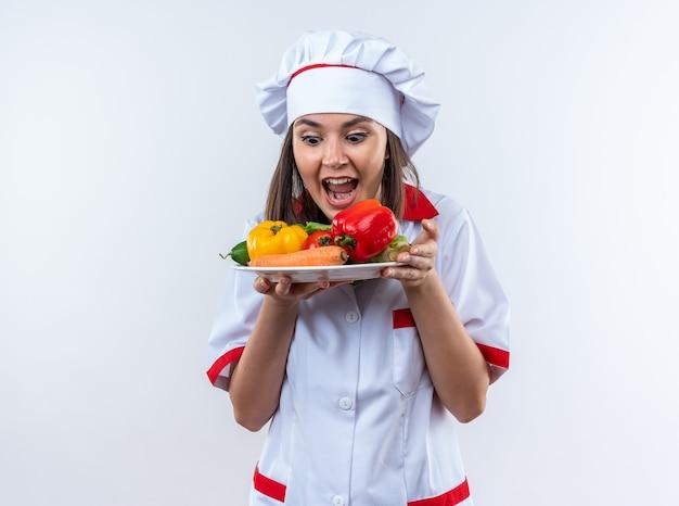 Opgewonden jonge vrouwelijke kok met een uniform van de chef-kok die groenten vasthoudt en kijkt naar groenten op een bord dat op een witte muur wordt geïsoleerd