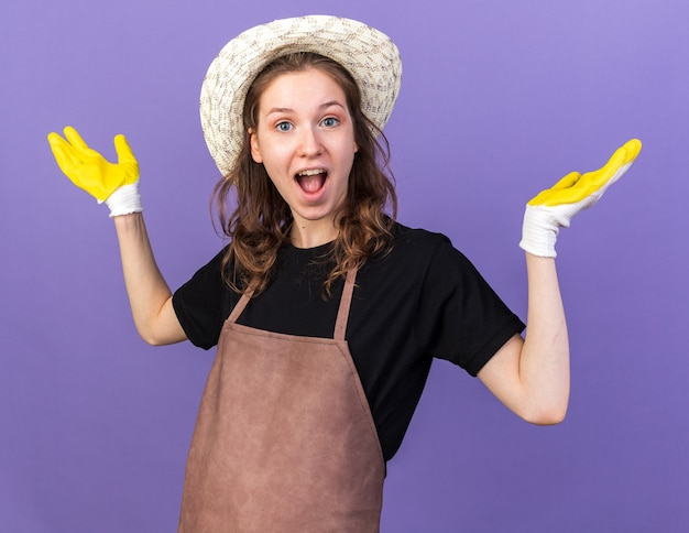 Opgewonden jonge vrouwelijke tuinman die een tuinhoed draagt met handschoenen die handen spreiden