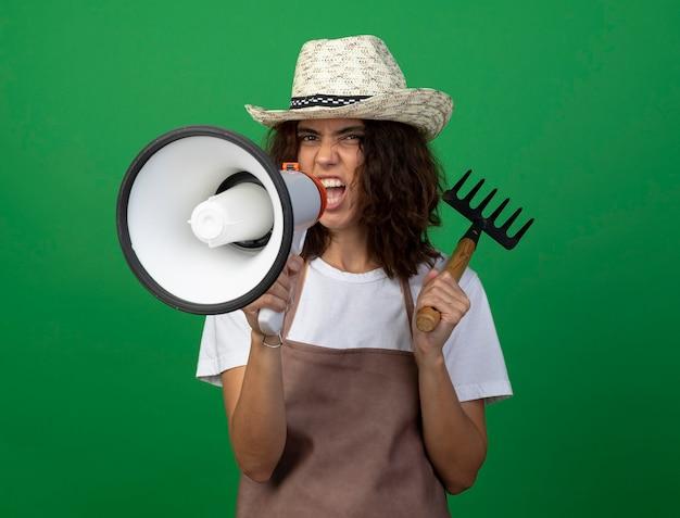 Opgewonden jonge vrouwelijke tuinman in uniform dragen tuinieren hoed hark zetten schouder en spreekt op luidspreker