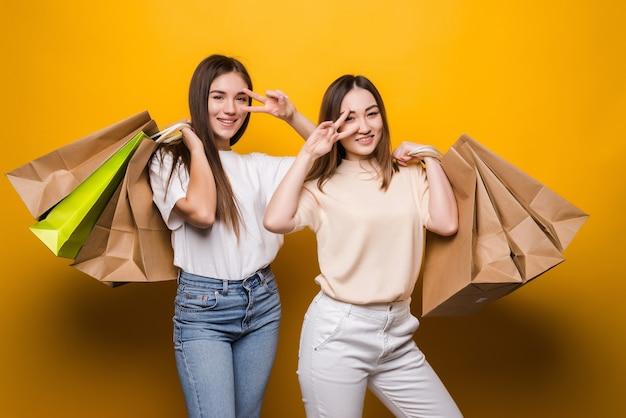 Opgewonden jonge vrouwen meisjes vrienden houden pakketzak met aankopen na het winkelen poseren geïsoleerd op gele muur. mensen levensstijl concept.