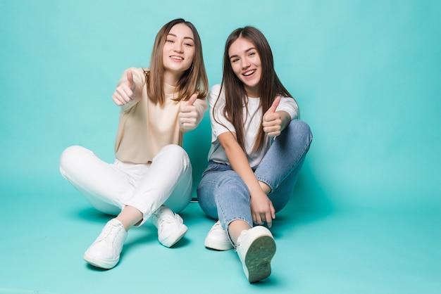 Opgewonden jonge vrouwen met duimen die omhoog op de vloer op turkooise muur stellen.