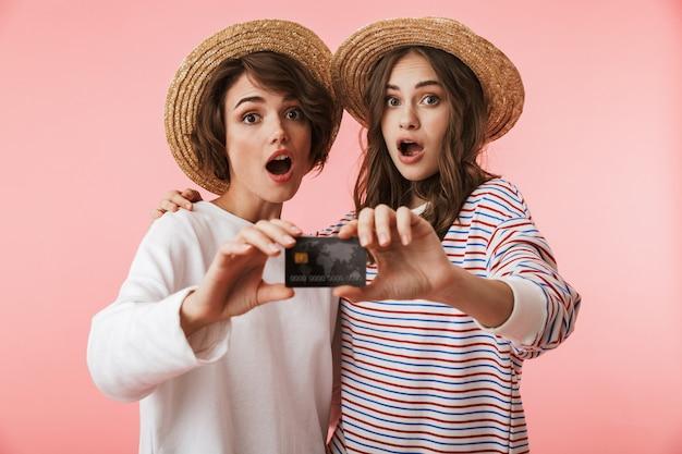 Opgewonden jonge vrouwenvrienden die over de roze creditcard van de muurholding worden geïsoleerd als achtergrond.