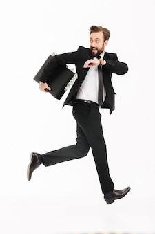 Opgewonden jonge zakenman met koffer lopen