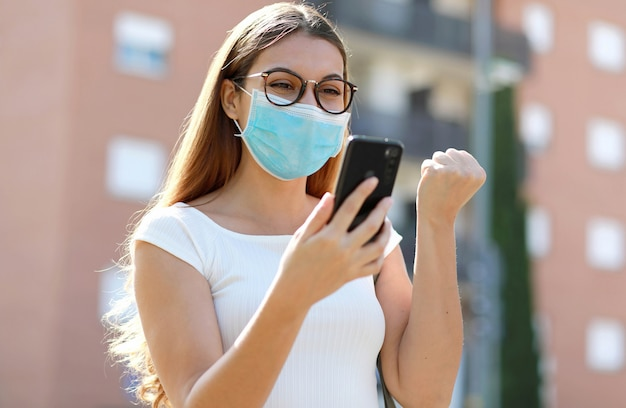 Opgewonden jonge zakenvrouw met chirurgische masker goed nieuws ontvangen op mobiele telefoon vieren met vuist omhoog in de moderne stadswijk