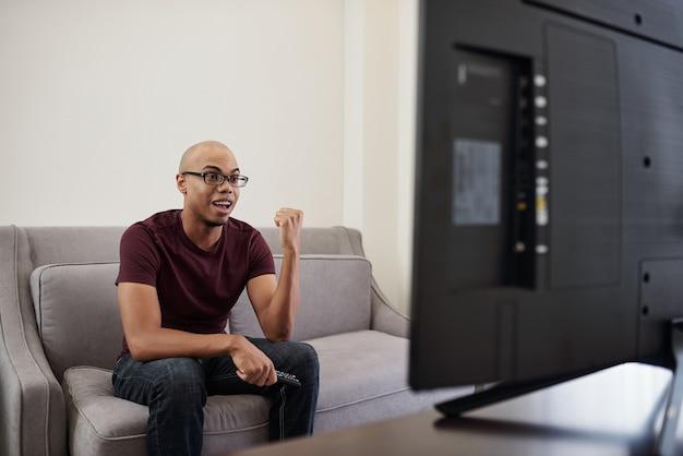 Opgewonden jonge zwarte man kijken naar sportwedstrijd op tv thuis