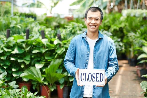 Opgewonden jongeman die tuincentrum sluit na grote verkoop