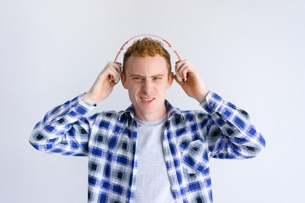 Opgewonden jongeman hoofdtelefoon houden in de buurt van oren