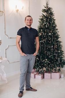 Opgewonden jongeman met handen in zakken feestelijk gevoel tijdens poseren in de buurt van een kerstboom. vakantie concept