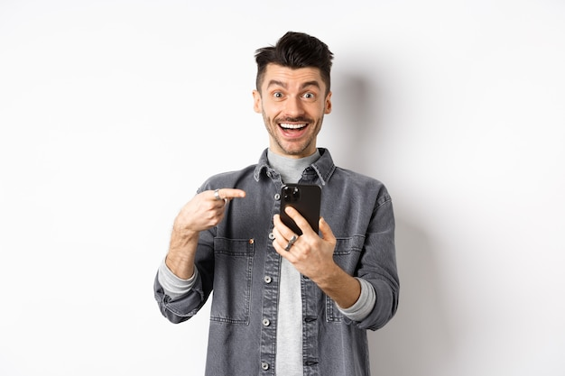Opgewonden jongeman ontvangt goed nieuws op de telefoon, wijzend op smartphone en glimlachend blij, staande op een witte achtergrond.