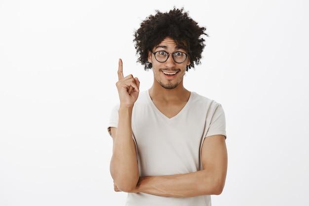 Opgewonden jongeman, student heeft een idee, vinger opsteken en gelukkig glimlachen