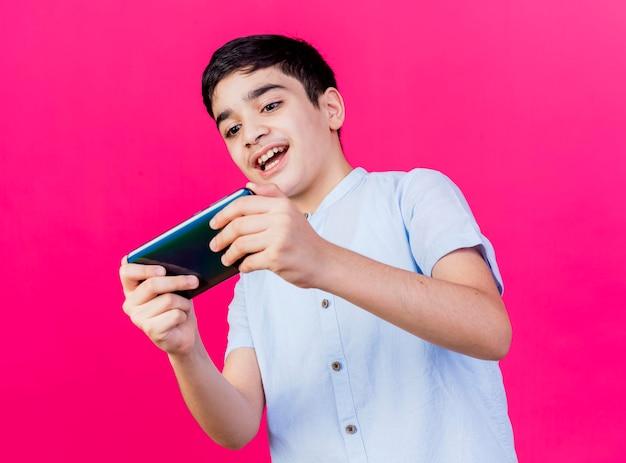 Opgewonden jongen speelspel op telefoon geïsoleerd op roze muur