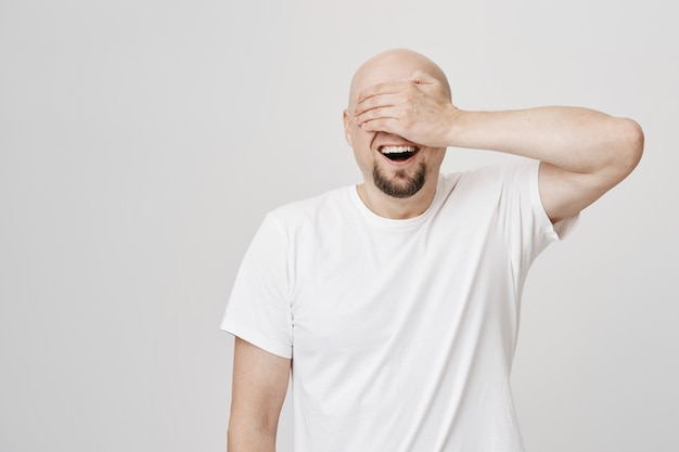 Opgewonden kale volwassen man met baard sluit ogen met palm, glimlachend