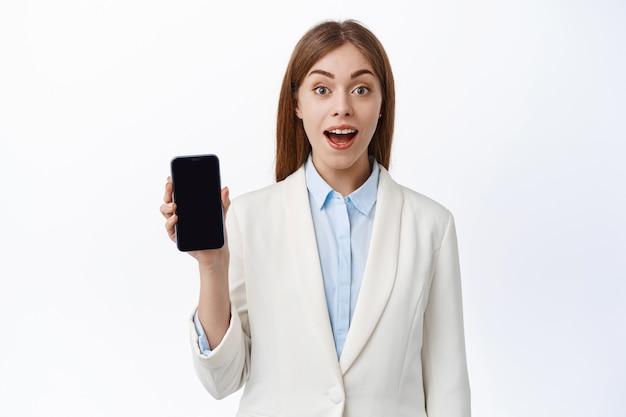 Opgewonden kantoordame in pak toont haar smartphonescherm, demonstreert geweldige app-functie, toont display, staat tegen witte muur