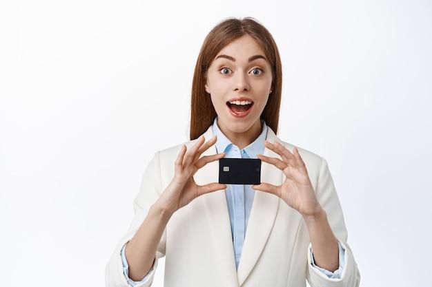Opgewonden kantoorvrouw, manager of ceo toont plastic creditcard en glimlacht verbaasd, beveelt bank aan, staat over witte muur