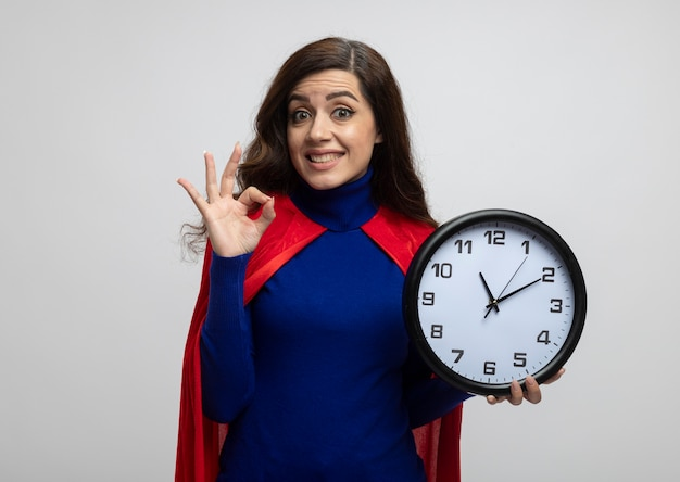 Opgewonden kaukasisch superheld meisje met rode cape gebaren ok handteken en houdt klok geïsoleerd op een witte muur met kopie ruimte