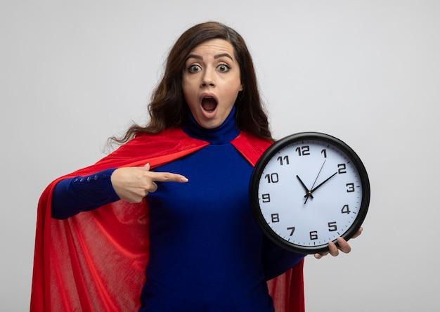 Opgewonden kaukasisch superheld meisje met rode cape houdt en wijst op klok op wit