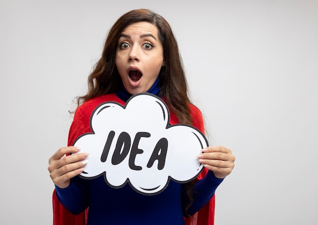 Opgewonden kaukasisch superheld meisje met rode cape houdt idee zeepbel op wit