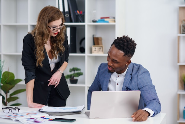 Opgewonden kaukasisch wijfje dat ideeën of businessplan deelt met zwarte mannelijke collega.