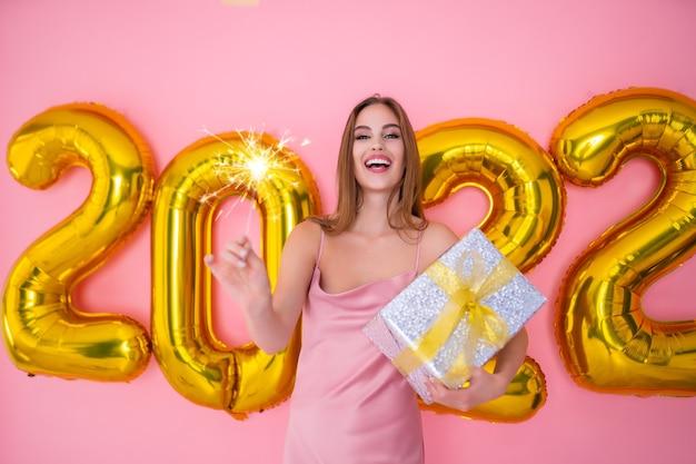 Opgewonden kerstmanmeisje laat champagne sprankelen terwijl ze nieuwjaarsballonnen in een geschenkdoos houdt