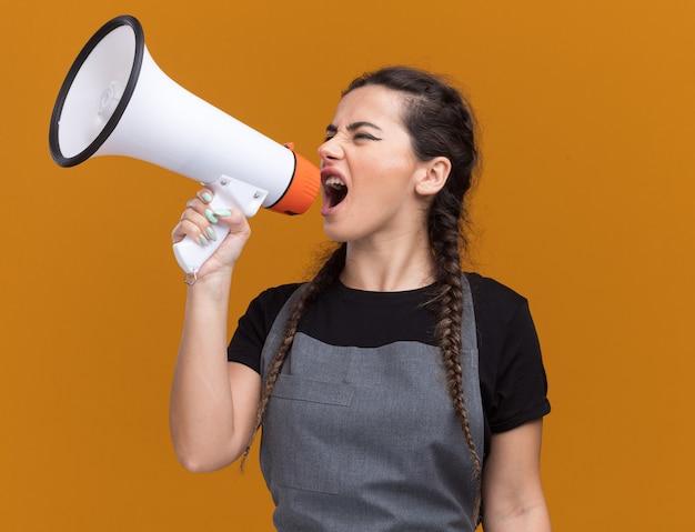 Opgewonden kijken naar de jonge vrouwelijke kapper aan de zijkant in uniform spreekt op luidspreker geïsoleerd op oranje muur