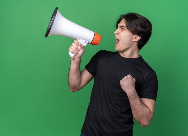Opgewonden kijken naar kant jonge knappe kerel die zwart t-shirt draagt, spreekt op luidspreker en toont ja gebaar geïsoleerd op groene muur