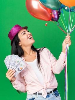 Opgewonden kijkende jonge, mooie vrouw met een feesthoed die ballonnen vasthoudt met contant geld geïsoleerd op een groene muur