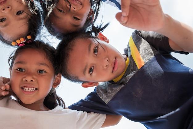 Opgewonden kinderen staan in cirkel knuffelen camera kijken om samen te spelen