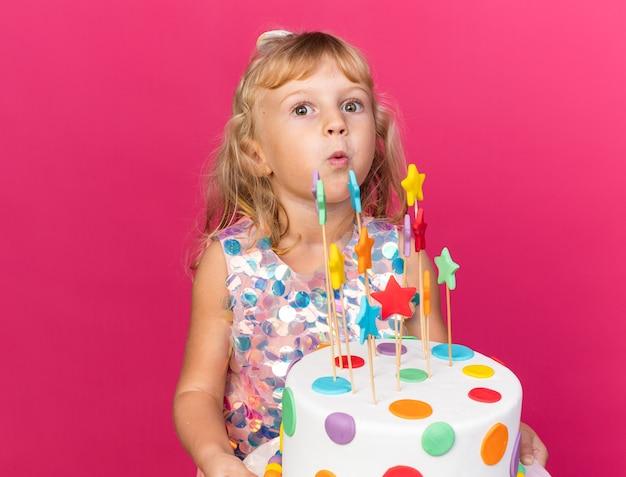 Opgewonden klein blond meisje met verjaardagstaart geïsoleerd op roze muur met kopieerruimte