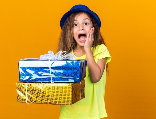 Opgewonden klein kaukasisch meisje met blauwe feestmuts die hand op het gezicht legt en geschenkdozen vasthoudt die op een oranje muur met kopieerruimte zijn geïsoleerd