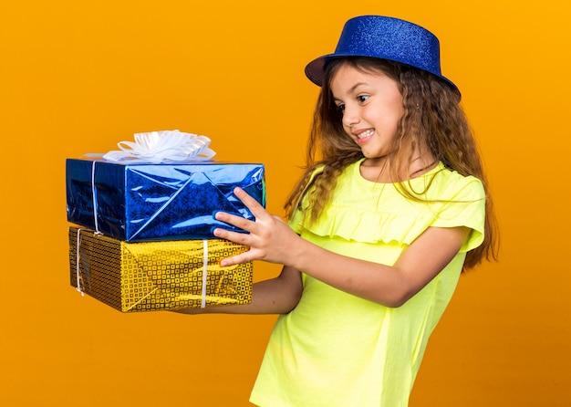 Opgewonden klein kaukasisch meisje met blauwe feestmuts houden en kijken naar geschenkdozen geïsoleerd op oranje muur met kopie ruimte