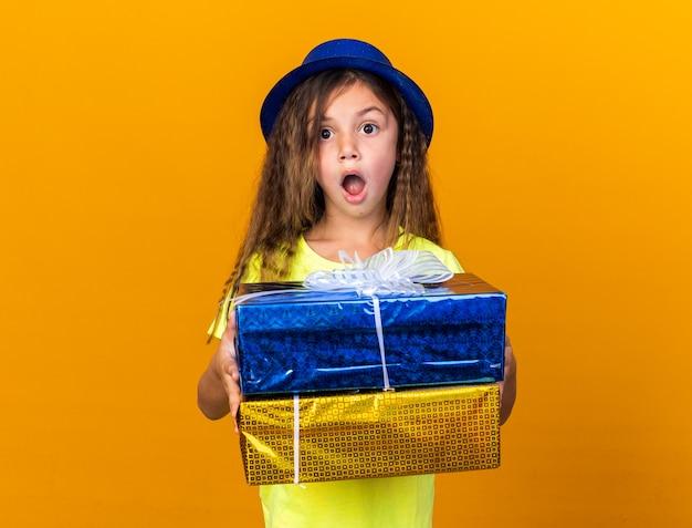 Opgewonden klein kaukasisch meisje met blauwe feestmuts met geschenkdozen geïsoleerd op oranje muur met kopie ruimte