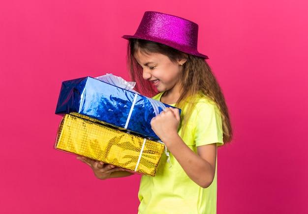 Opgewonden klein kaukasisch meisje met paarse feestmuts die geschenkdozen vasthoudt en vuist geïsoleerd houdt op roze muur met kopieerruimte