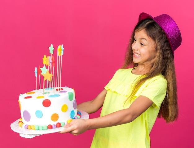 Opgewonden klein kaukasisch meisje met paarse feestmuts die verjaardagstaart vasthoudt en bekijkt, geïsoleerd op roze muur met kopieerruimte