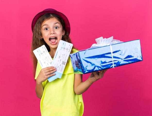 Opgewonden klein kaukasisch meisje met paarse feestmuts met geschenkdoos en vliegtickets geïsoleerd op roze muur met kopieerruimte