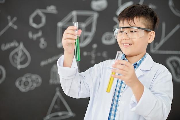 Opgewonden kleine wetenschapper die reageerbuizen met groene en gele vloeistoffen in zijn handen bekijkt