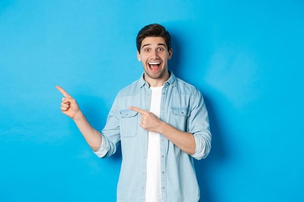 Opgewonden knappe 25-jarige man met baard, wijzende vingers naar links en glimlachend verbaasd, staande tegen een blauwe achtergrond.