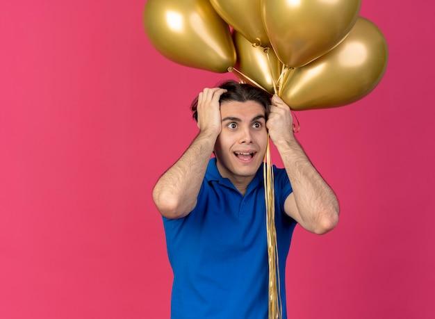 Opgewonden knappe blanke man met blauwe feesthoed zet handen op het hoofd met heliumballonnen