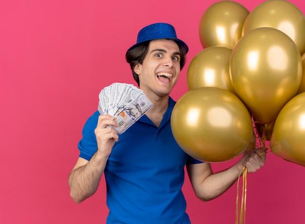 Opgewonden knappe blanke man met blauwe feestmuts houdt heliumballonnen en geld vast