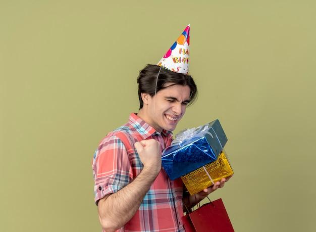 Opgewonden knappe blanke man met verjaardagspet houdt de vuist vast met geschenkdozen en papieren boodschappentas
