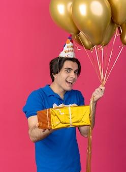 Opgewonden knappe blanke man met verjaardagspet houdt heliumballonnen en geschenkdoos vast