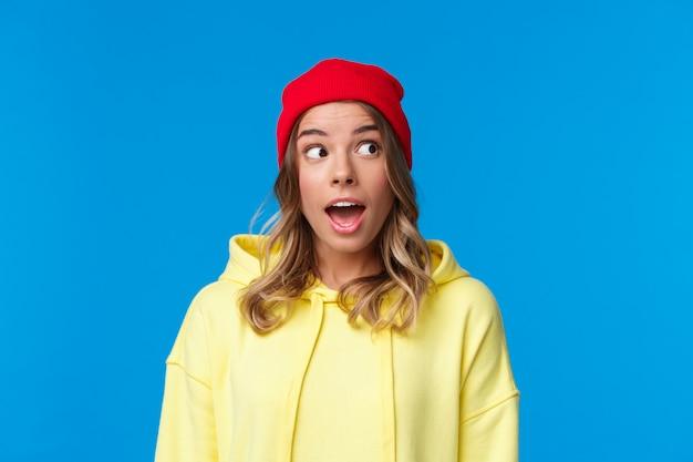 Opgewonden knappe blanke studente in rode muts en gele hoodie, kijk rechtsboven en open mond gefascineerd, hoor interessante roddel, staand