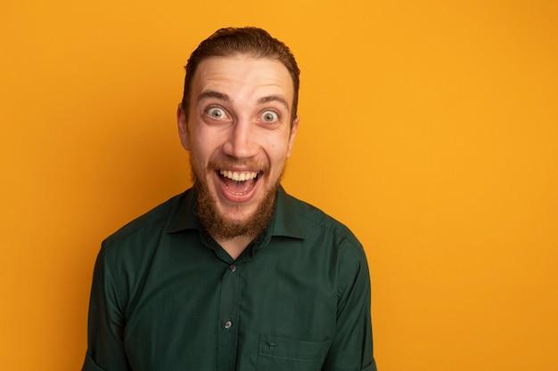 Opgewonden knappe blonde man camera kijken op oranje