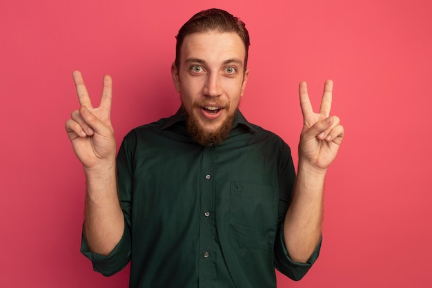 Opgewonden knappe blonde man gebaren overwinning handteken met twee handen geïsoleerd op roze muur