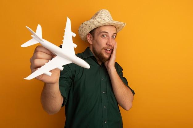Opgewonden knappe blonde man met strandhoed houdt modelvliegtuig geïsoleerd op oranje muur