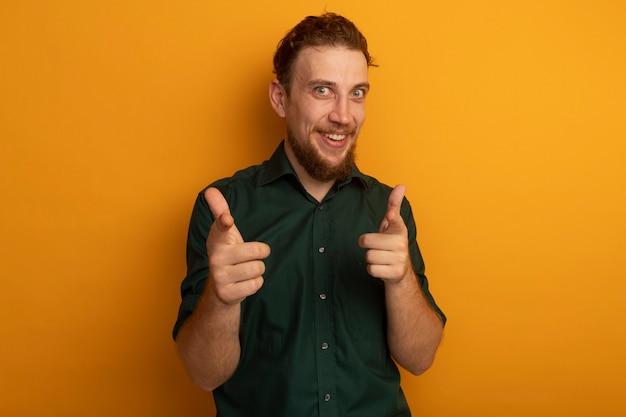 Opgewonden knappe blonde man wijst op camera met twee handen op sinaasappel