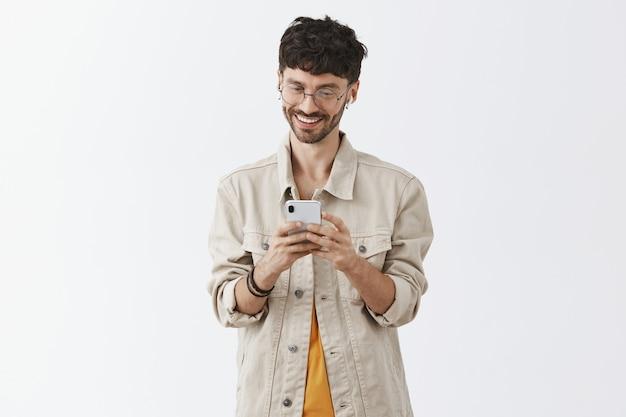 Opgewonden knappe jongeman met behulp van mobiele telefoon en op zoek gelukkig