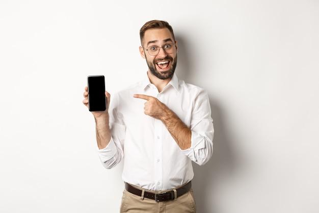 Opgewonden knappe kerel die mobiele telefoon toont, vinger op scherm richt en glimlacht, die zich tegen witte achtergrond bevindt.